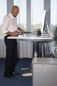 Mann arbeitet am hochgefahrenen Schreibtisch