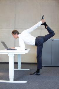 Mann macht gymnastische Übung am nicht ausreichend hoehenverstellbaren Schreibtisch